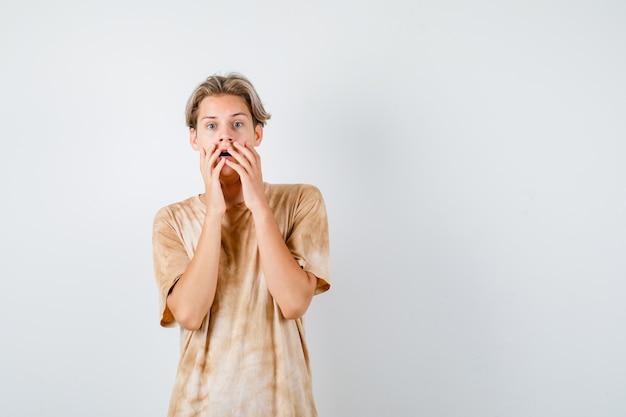 Jonge tienerjongen houdt handen in de buurt van open mond in t-shirt en kijkt verrast. vooraanzicht.