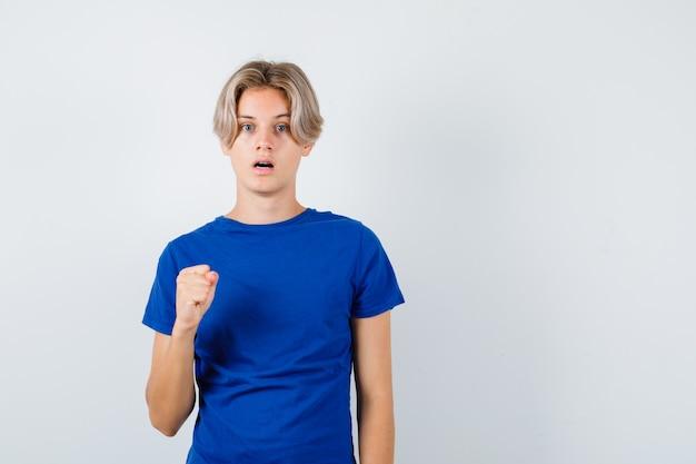 Jonge tienerjongen in blauw t-shirt met gebalde vuist en verbaasd, vooraanzicht.