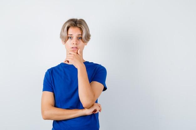 Jonge tienerjongen in blauw t-shirt met hand op kin en somber, vooraanzicht.