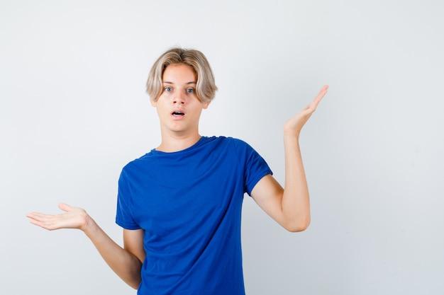 Jonge tienerjongen in blauw t-shirt met hulpeloos gebaar en verbaasd, vooraanzicht.
