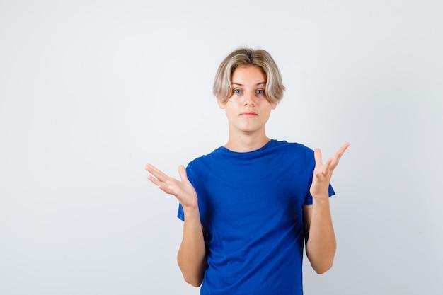 Jonge tienerjongen in blauw t-shirt met hulpeloos gebaar en verbijsterd, vooraanzicht.