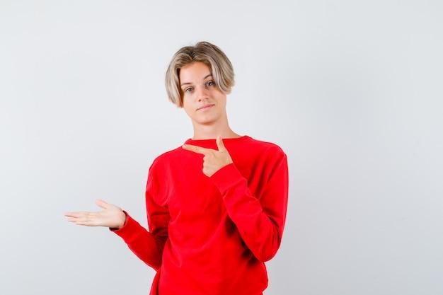 Jonge tienerjongen in een rode trui die naar links wijst, de handpalm opzij spreidt en er zelfverzekerd uitziet, vooraanzicht.