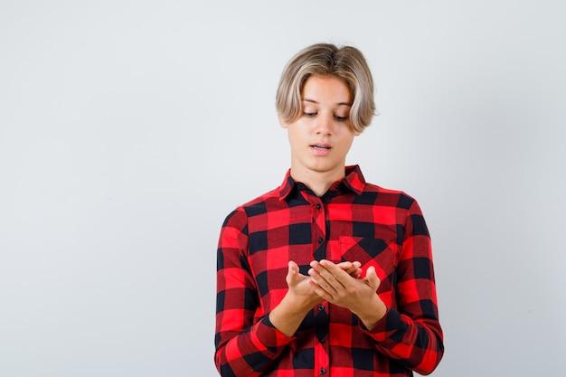 Jonge tienerjongen in geruit hemd die naar zijn handpalm kijkt en er attent uitziet, vooraanzicht.