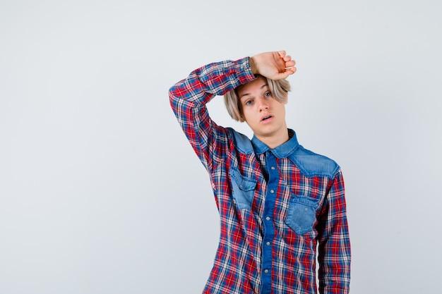 Jonge tienerjongen in geruit overhemd die de hand op het hoofd houdt en er bedroefd uitziet, vooraanzicht.
