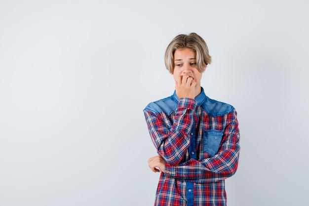 Jonge tienerjongen in geruit overhemd die nagels bijt terwijl hij naar beneden kijkt en angstig kijkt, vooraanzicht.