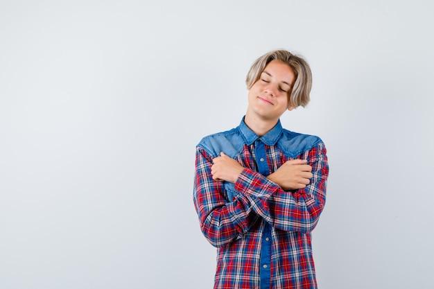 Jonge tienerjongen in geruit overhemd knuffelt zichzelf, houdt zijn ogen dicht en ziet er vredig uit, vooraanzicht. Premium Foto
