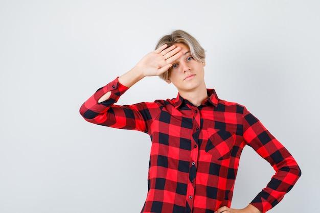 Jonge tienerjongen in geruit overhemd met hand op voorhoofd en droevig kijkend, vooraanzicht.