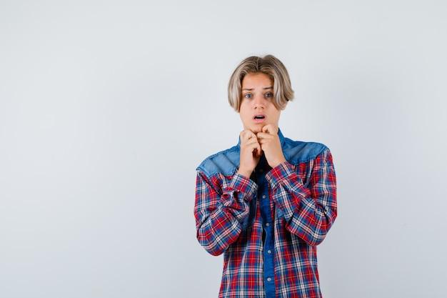 Jonge tienerjongen in geruit overhemd met handen op kin en opgewonden kijkend