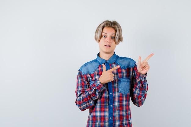 Jonge tienerjongen in geruit overhemd wijzend naar de rechterbovenhoek en verbaasd kijkend