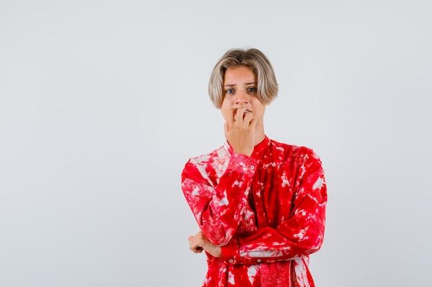 Jonge tienerjongen in hemd die emotioneel nagels bijt en er angstig uitziet, vooraanzicht.