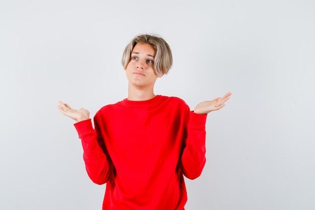 Jonge tienerjongen in rode trui die hulpeloos gebaar toont en peinzend kijkt, vooraanzicht.
