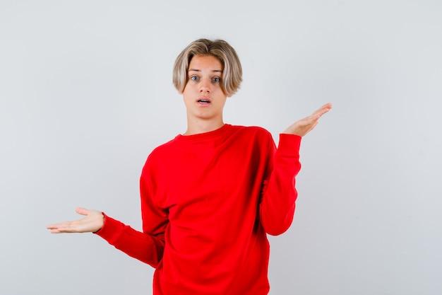 Jonge tienerjongen in rode trui die hulpeloos gebaar toont en verbaasd kijkt, vooraanzicht.