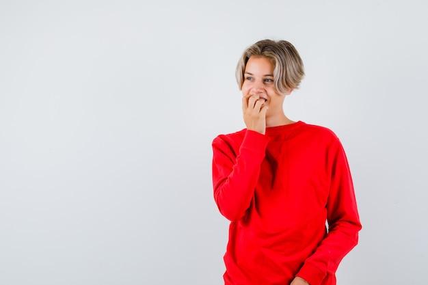 Jonge tienerjongen in rode trui die nagels bijt terwijl hij wegkijkt en er gelukkig uitziet, vooraanzicht.