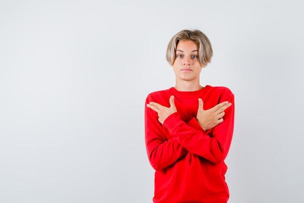 Jonge tienerjongen in rode trui die pistoolgebaar toont en besluiteloos kijkt, vooraanzicht.