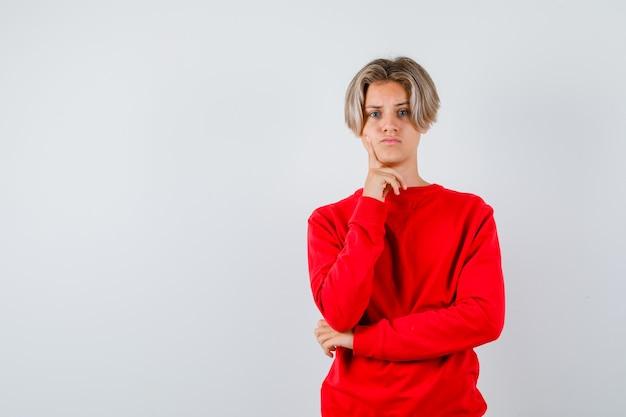 Jonge tienerjongen in rode trui die vinger op de wang houdt en er verdrietig uitziet, vooraanzicht.