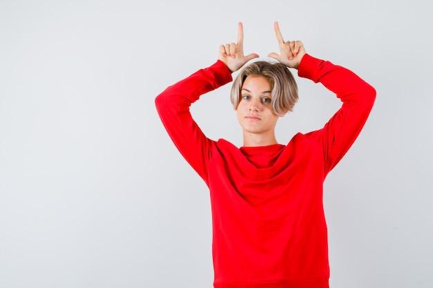 Jonge tienerjongen in rode trui die vingers boven het hoofd houdt als hoorns en er grappig uitziet, vooraanzicht.