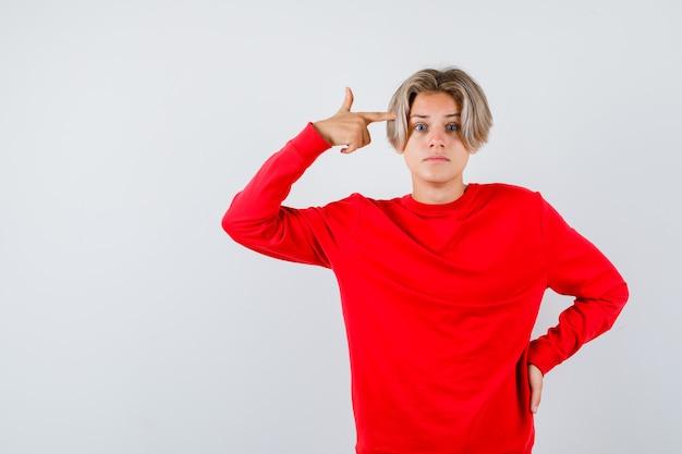Jonge tienerjongen in rode trui die zelfmoordgebaar toont en verbaasd kijkt, vooraanzicht.