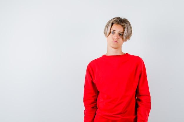 Jonge tienerjongen in rode trui en teleurgesteld, vooraanzicht.