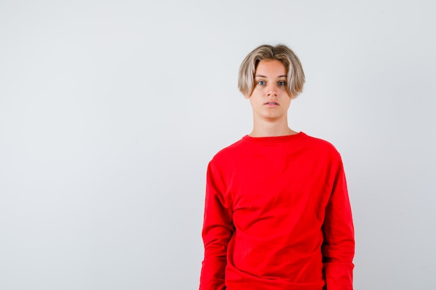 Jonge tienerjongen in rode trui en verbaasd, vooraanzicht.