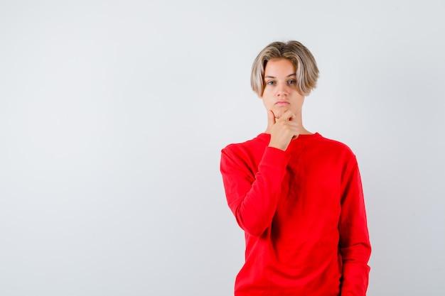 Jonge tienerjongen in rode trui met hand op kin en attent, vooraanzicht.