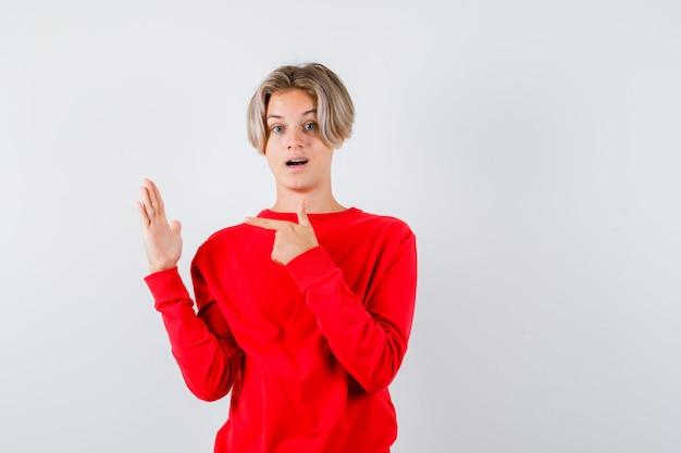 Jonge tienerjongen in rode trui wijzend naar zijn opgeheven hand en besluiteloos kijkend, vooraanzicht.