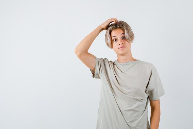 Jonge tienerjongen in t-shirt die aan zijn hoofd krabt en verbaasd kijkt