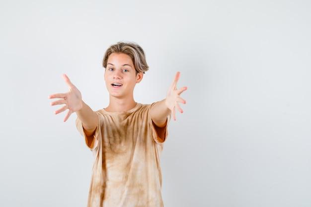 Jonge tienerjongen in t-shirt die armen opent voor knuffel en er vrolijk uitziet, vooraanzicht.