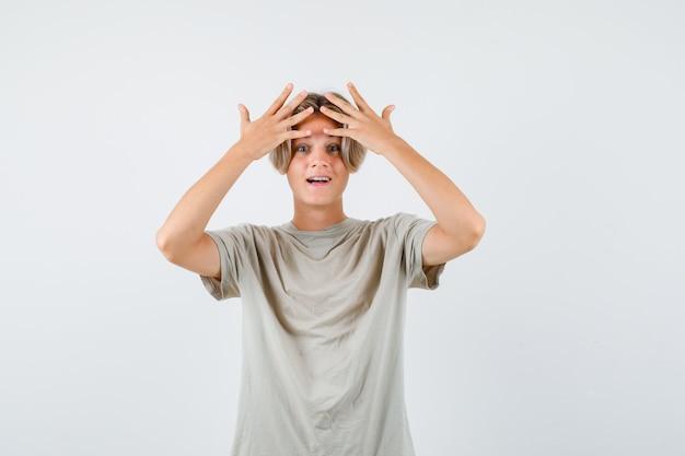 Jonge tienerjongen in t-shirt die de handen op het hoofd houdt en er gelukkig uitziet, vooraanzicht.
