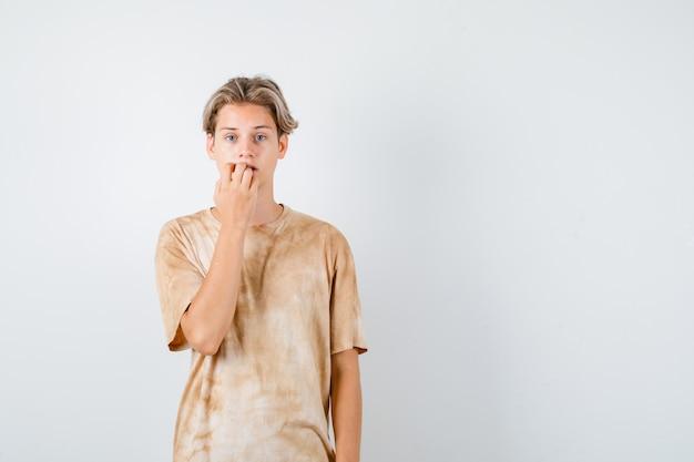 Jonge tienerjongen in t-shirt die emotioneel nagels bijt en er angstig uitziet, vooraanzicht.