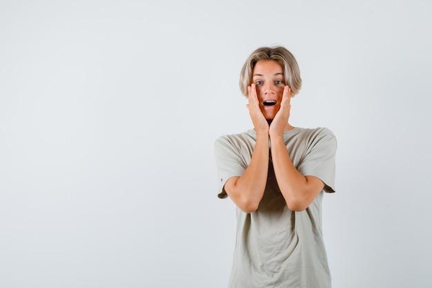 Jonge tienerjongen in t-shirt die handen op de wangen houdt en er angstig uitziet