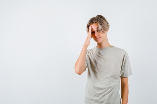 Jonge tienerjongen in t-shirt die hoofdpijn heeft en er vermoeid uitziet