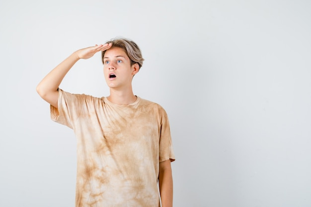 Jonge tienerjongen in t-shirt die ver weg kijkt met de hand boven het hoofd en zich afvraagt, vooraanzicht.