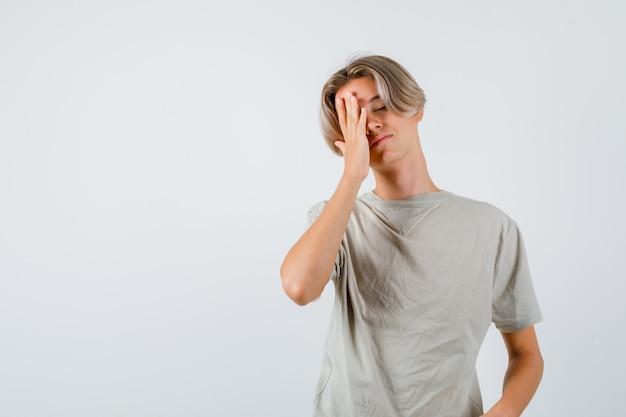 Jonge tienerjongen in t-shirt die zijn hand op zijn gezicht houdt en er vermoeid uitziet