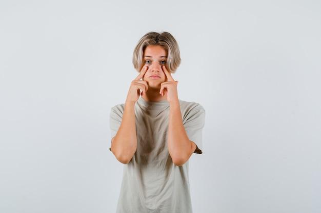 Jonge tienerjongen in t-shirt wijzend naar zijn oogleden en verdrietig kijkend