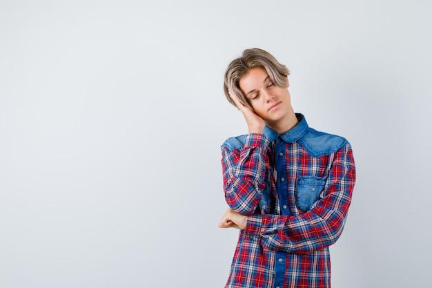 Jonge tienerjongen leunend op palm als kussen in geruit overhemd en ziet er moe uit, vooraanzicht.
