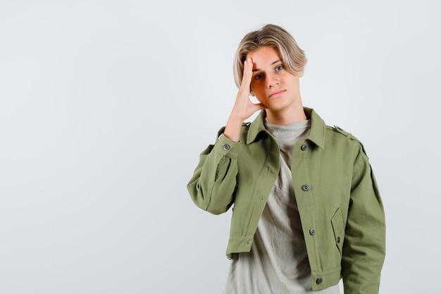 Jonge tienerjongen leunt met zijn hoofd in t-shirt, jas en kijkt boos. vooraanzicht.