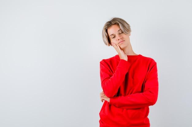 Jonge tienerjongen leunt wang aan de hand in rode trui en ziet er ontspannen uit, vooraanzicht.