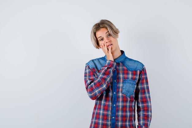 Jonge tienerjongen leunt wang bij de hand in geruit overhemd en ziet er somber uit. vooraanzicht.