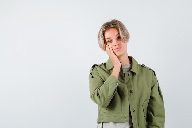 Jonge tienerjongen leunt wang op palm in groene jas en kijkt peinzend. vooraanzicht.
