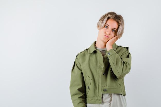 Jonge tienerjongen leunt wang op palm in groene jas en kijkt wanhopig. vooraanzicht.