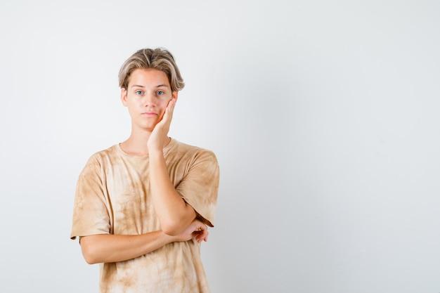 Jonge tienerjongen leunt wang op palm in t-shirt en kijkt teleurgesteld, vooraanzicht.