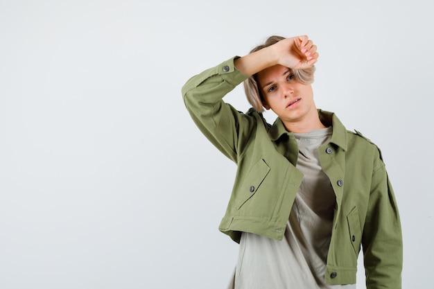 Jonge tienerjongen met arm op voorhoofd in groene jas en wanhopig op zoek