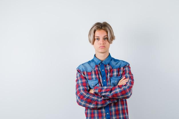 Jonge tienerjongen met armen gevouwen in geruit overhemd en somber kijkend. vooraanzicht.