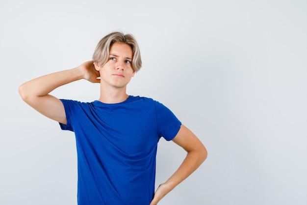 Jonge tienerjongen met hand achter hoofd, omhoog kijkend in blauw t-shirt en peinzend kijkend, vooraanzicht.