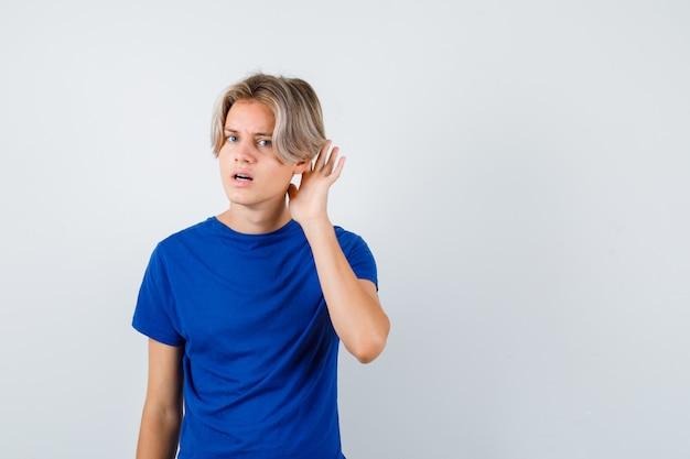 Jonge tienerjongen met hand achter oor in blauw t-shirt en verward kijkend. vooraanzicht.