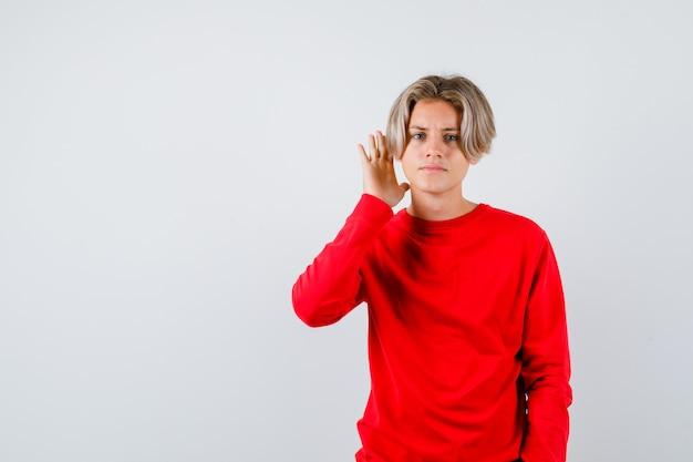 Jonge tienerjongen met hand dichtbij oor in rode sweater en verward kijkend. vooraanzicht.