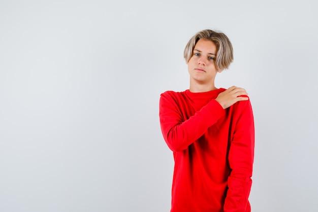 Jonge tienerjongen met hand op schouder in rode trui en ziet er moe uit. vooraanzicht.