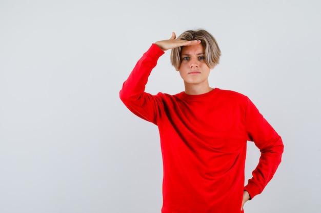 Jonge tienerjongen met hand over hoofd in rode sweater en verward kijkend. vooraanzicht.