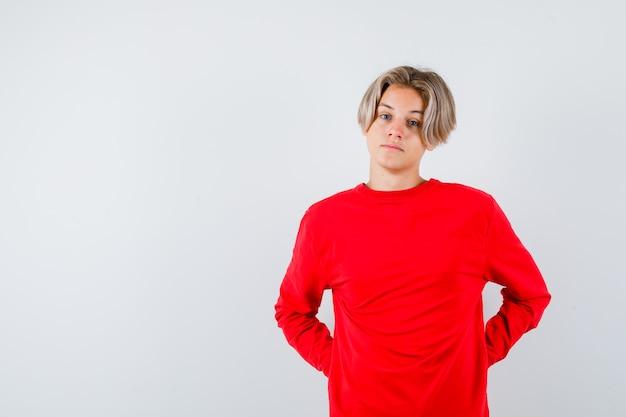 Jonge tienerjongen met handen achter rug in rode trui en peinzend kijkend, vooraanzicht.