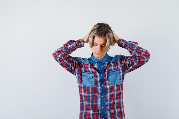 Jonge tienerjongen met handen op hoofd